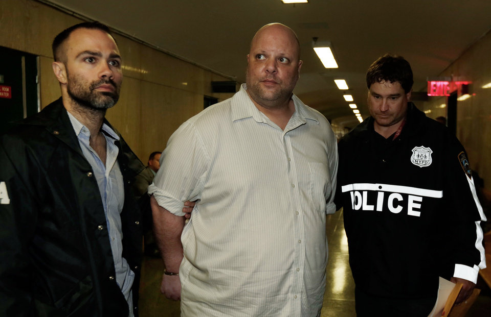 Photo - Carmine Vitolo, center, a manager of a strip club in the Queens borough of New York, is escorted in handcuffs to court by police, in New York, Wednesday, June 11, 2014.  Drug Enforcement Administration and New York Police Department investigators arrested four women, all described as professional strippers, and Vitolo, on charges including grand larceny, assault and forgery. They were accused of scamming wealthy men by spiking their drinks with illegal synthetic drugs, then driving them to strip clubs that ran up tens of thousands of dollars on their credit cards while they were too intoxicated to stop it, authorities said Wednesday.  (AP Photo/Richard Drew)