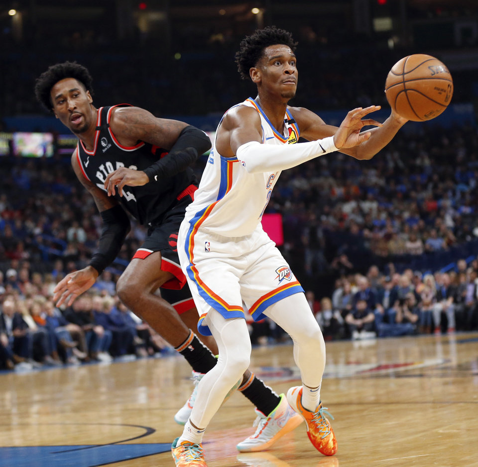 Photo - Oklahoma City's Shai Gilgeous-Alexander (2) passes away from Toronto's Rondae Hollis-Jefferson (4) in the first quarter during an NBA basketball between the Oklahoma City Thunder and the Toronto Raptors at Chesapeake Energy Arena in Oklahoma City, Wednesday, Jan. 15, 2020. [Nate Billings/The Oklahoman]