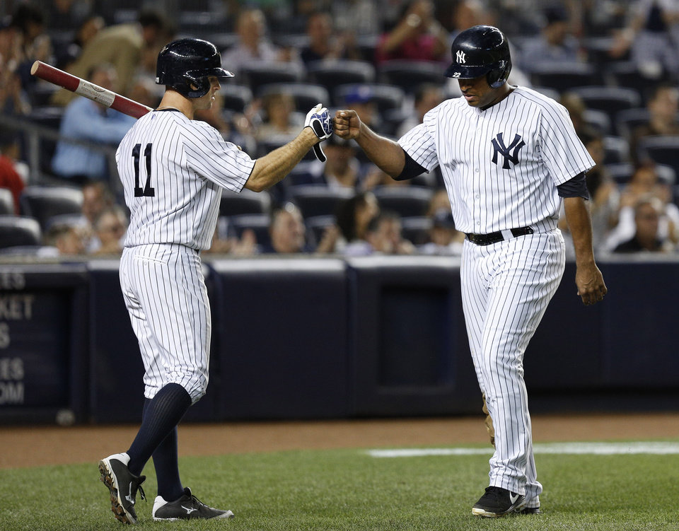 New York Yankees\' Vernon Wells (22) celebrates with Brett Gardner (11) after stealing home in the second inning of a baseball game against the Chicago White Sox at Yankee Stadium, Tuesday, Sept. 3, 2013, in New York. (AP Photo/John Minchillo)