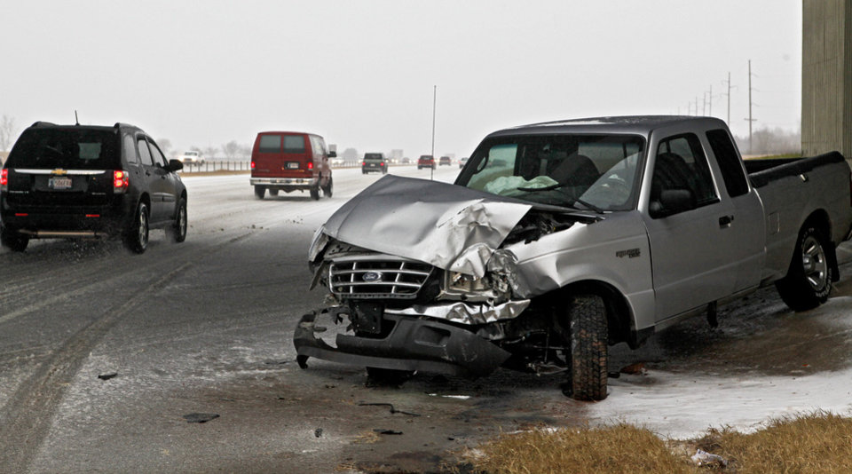 Photo - BLIZZARD / ICE / WINTER WEATHER / TRUCK ACCIDENT / WRECK / SNOWSTORM / SNOW: Traffic navigates its way on icy roads past the remains of an injury accident on Lake Hefner Parkway on Thursday Dec. 24, 2009, in Oklahoma City, Okla.   Photo by Chris Landsberger, The Oklahoman ORG XMIT: KOD
