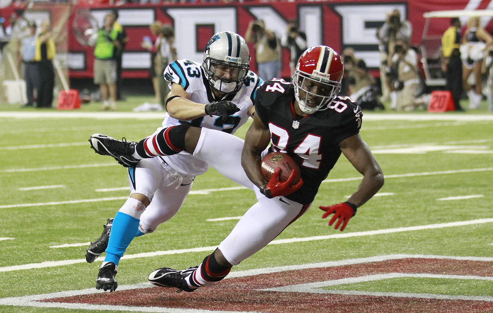 "ADVANCE FOR WEEKEND EDITIONS, OCT. 6-7 - FILE - This Sept. 30, 2012 file photo shows Atlanta Falcons wide receiver Roddy White (84) catching a touchdown pass as Carolina Panthers free safety Haruki Nakamura (43) defends during the first half of an NFL football game, in Atlanta. White showed up at his locker with a somber look. ""We're all business this week,"" he said. But it wasn't long before the Falcons receiver broke into a big smile. (AP Photo/John Bazemore)"