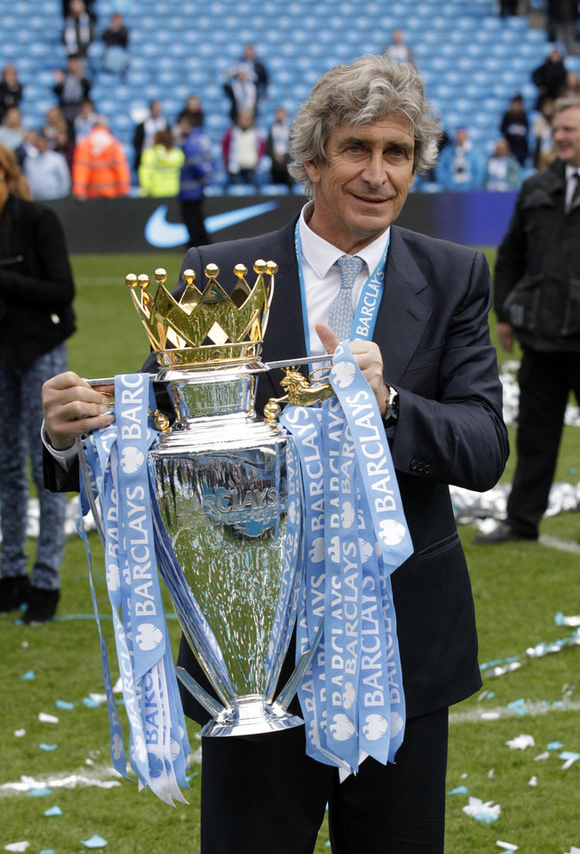 Photo - Manchester City's manager Manuel Pellegrini poses for photographers with the trophy after the English Premier League soccer match between Manchester City and West Ham at the Etihad Stadium in Manchester, England, Sunday May 11, 2014.  Manchester City won the Premier League for the second time in three seasons on Sunday, completing its campaign with a comfortable 2-0 victory over West Ham that lacked any of the drama of its previous title.  (AP Photo/Jon Super)