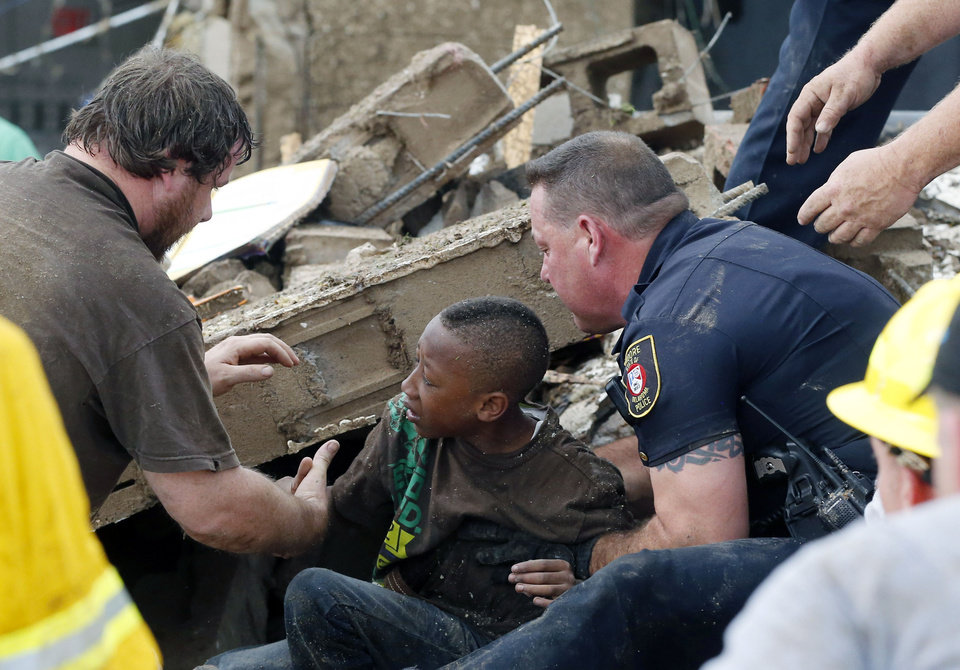 A boy is pulled from beneath a collapsed wall at the Plaza Towers Elementary School following a tornado in Moore, Okla., Monday, May 20, 2013. A tornado as much as a mile (1.6 kilometers) wide with winds up to 200 mph (320 kph) roared through the Oklahoma City suburbs Monday, flattening entire neighborhoods, setting buildings on fire and landing a direct blow on an elementary school. (AP Photo/ Sue Ogrocki) ORG XMIT: OKSO123