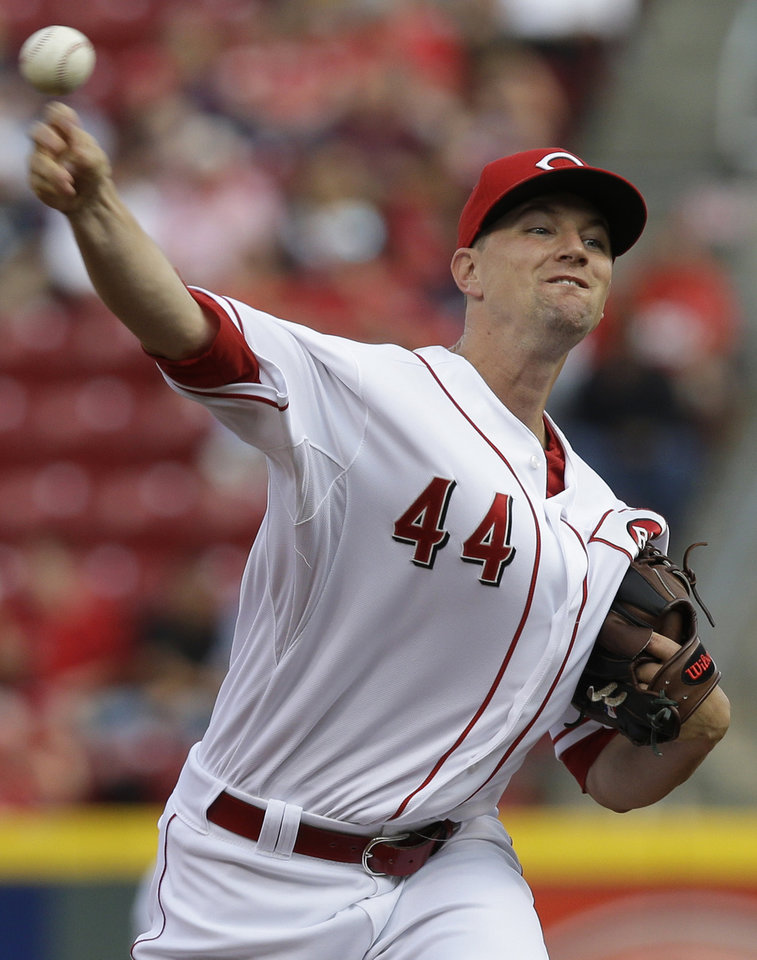 Photo - Cincinnati Reds starting pitcher Mike Leake throws against the Arizona Diamondbacks in the first inning of a baseball game, Tuesday, July 29, 2014, in Cincinnati. (AP Photo/Al Behrman)