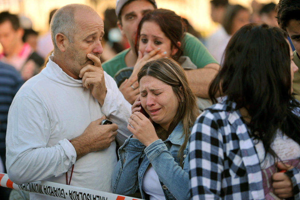 Photo - Relatives of victims react as they wait for news in fron of the Kiss nightclub in Santa Maria city,  Rio Grande do Sul state, Brazil, Sunday, Jan. 27, 2013.  According to police more than 200 died in the devastating nightclub fire in southern Brazil.  Officials say the fire broke out at the club while a band was performing. (AP Photo/Ronald Mendes-Agencia RBS)