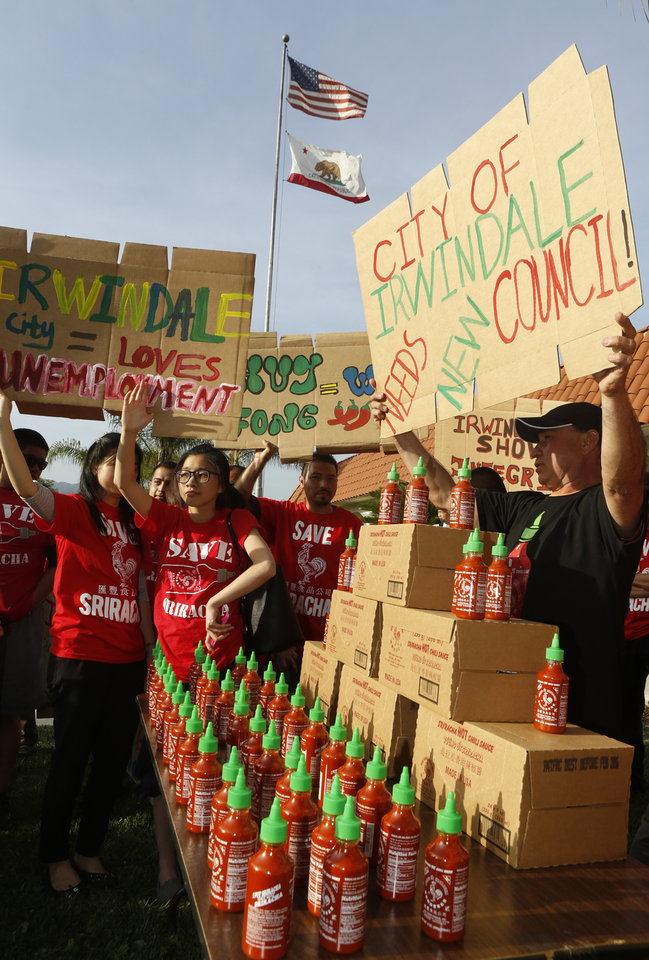 Photo - Sriracha hot sauce supporters protest ahead of the city council meeting in Irwindale, Calif., Wednesday, April 23, 2014. The Irwindale City Council has declared that the factory that produces the popular Sriracha hot sauce is a public nuisance. (AP Photo/Damian Dovarganes)