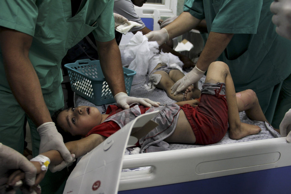 Photo - Palestinian doctors treat children wounded in an Israeli airstrike on a building, at the treatment room of al Najar hospital in Rafah in the southern Gaza Strip, Thursday, Aug. 21, 2014. (AP Photo/Hatem Ali)