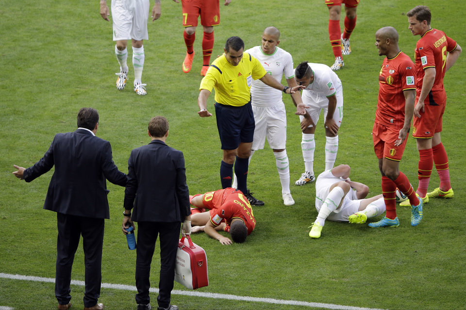 Photo - Referee Marco Rodriguez from Mexico gestures as head coach Marc Wilmots, left,  protests after Belgium's Eden Hazard, center, collided with Algeria's Mehdi Mostefa, third from right, during the group H World Cup soccer match between Belgium and Algeria at the Mineirao Stadium in Belo Horizonte, Brazil, Tuesday, June 17, 2014. At right is Belgium's Jan Vertonghen, second from right is Belgium's Vincent Kompany. Center is Algeria's Sofiane Feghouli. (AP Photo/Sergei Grits)