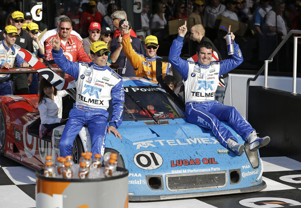Ganassi Racing team drivers, from front left, Scott Pruett; Charlie Kimball; Memo Rojas, of Mexico; and Juan Pablo Montoya, driving the car, of Colombia, arrive in Victory Lane after winning the Grand-Am Series Rolex 24 hour auto race at Daytona International Speedway, Sunday, Jan. 27, 2013, in Daytona Beach, Fla. (AP Photo/John Raoux)