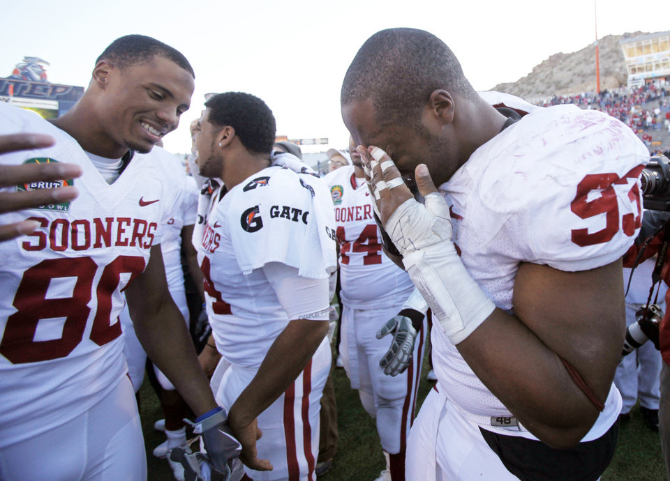 Photo - Gerald McCoy (93) wipes the tears from his eyes as he celebrates with Adron Tennell (80) after the 31-27 win over Stanford in the Brut Sun Bowl college football game between the University of Oklahoma Sooners (OU) and the Stanford University Cardinal on Thursday, Dec. 31, 2009, in El Paso, Tex.   Photo by Chris Landsberger, The Oklahoman