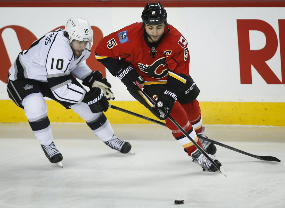 Photo - Los Angeles Kings' Mike Richards, left, gets his stick between the legs of Calgary Flames' Mark Giordano during second period NHL hockey action in Calgary, Alberta, Monday, March 10, 2014. (AP Photo/The Canadian Press, Jeff McIntosh)