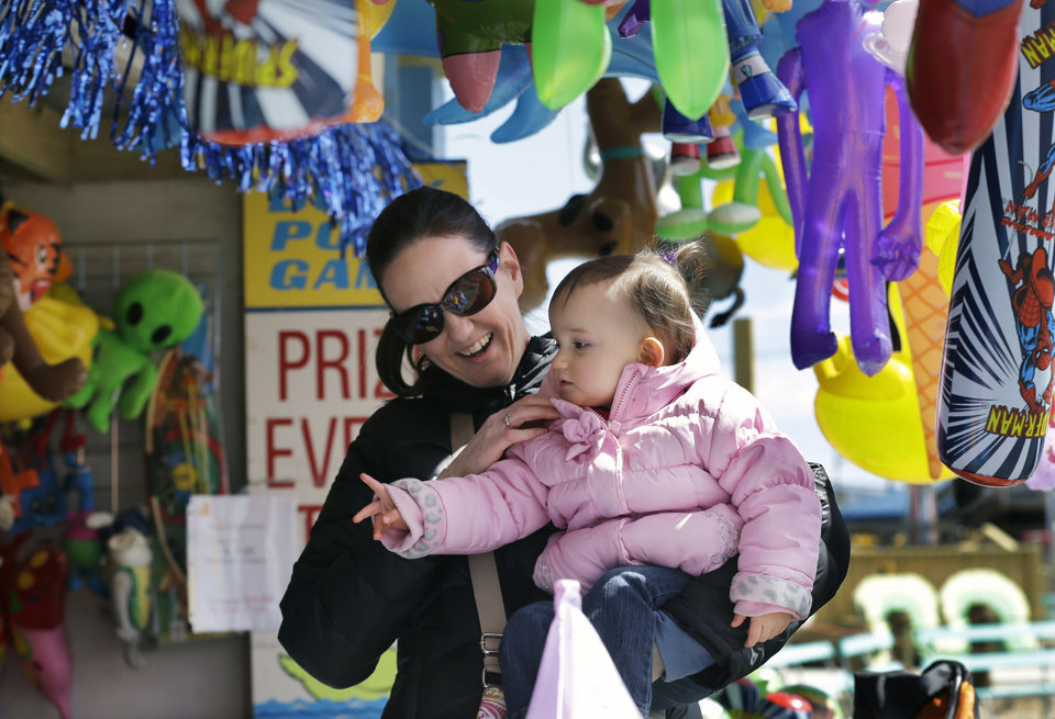 One-year-old Hunter Norrish shows her mother, Kim Norrish, of Delran, N.J., that she wants to play a duck pond game on opening day at The Keansburg Amusement Park, Saturday, March 23, 2013, in Keansburg, N.J. Founded in 1904, the Keansburg Amusement Park, which Superstorm Sandy left under up to six feet of water, opens Saturday even though not all rides will be ready to operate and its popular Wildcat roller coaster is gone. (AP Photo/Mel Evans)