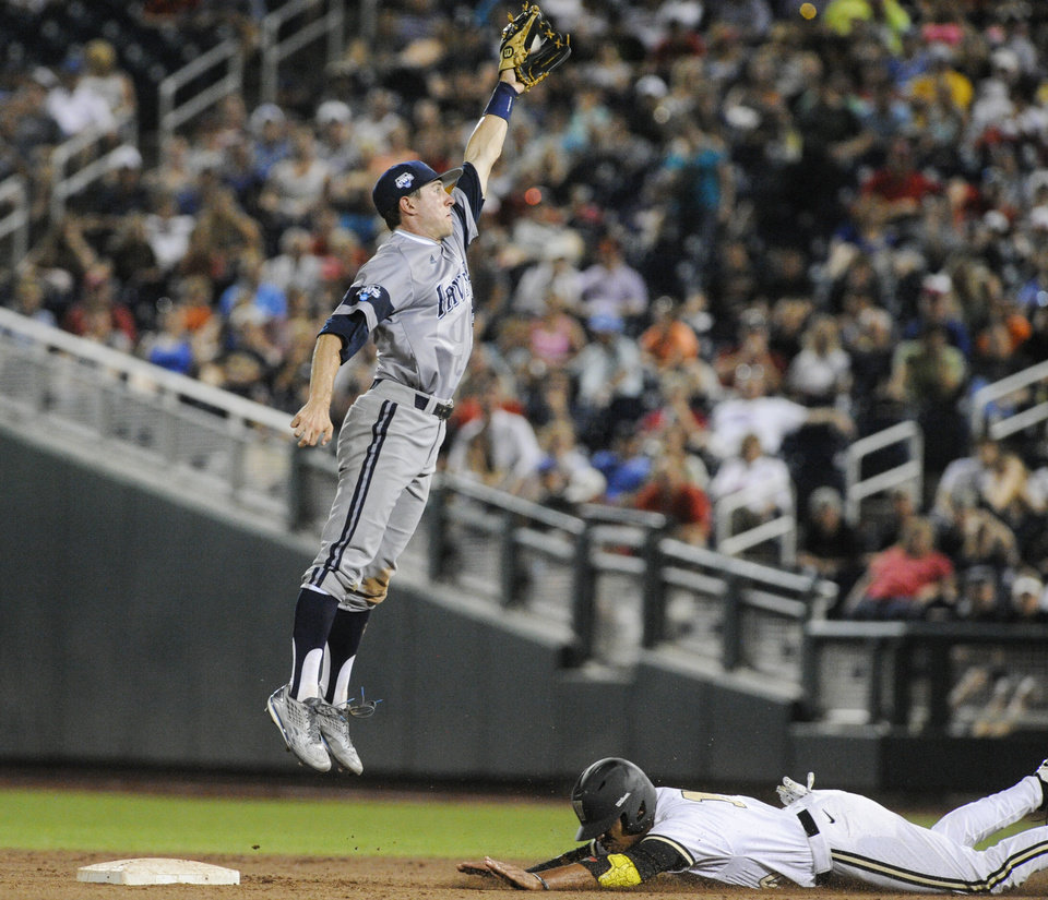 Photo - UC Irvine second baseman Grant Palmer (27) leaps to catch the ball as Vanderbilt's John Norwood steals second base in seventh the inning of an NCAA baseball College World Series game in Omaha, Neb., Monday, June 16, 2014. (AP Photo/Eric Francis)