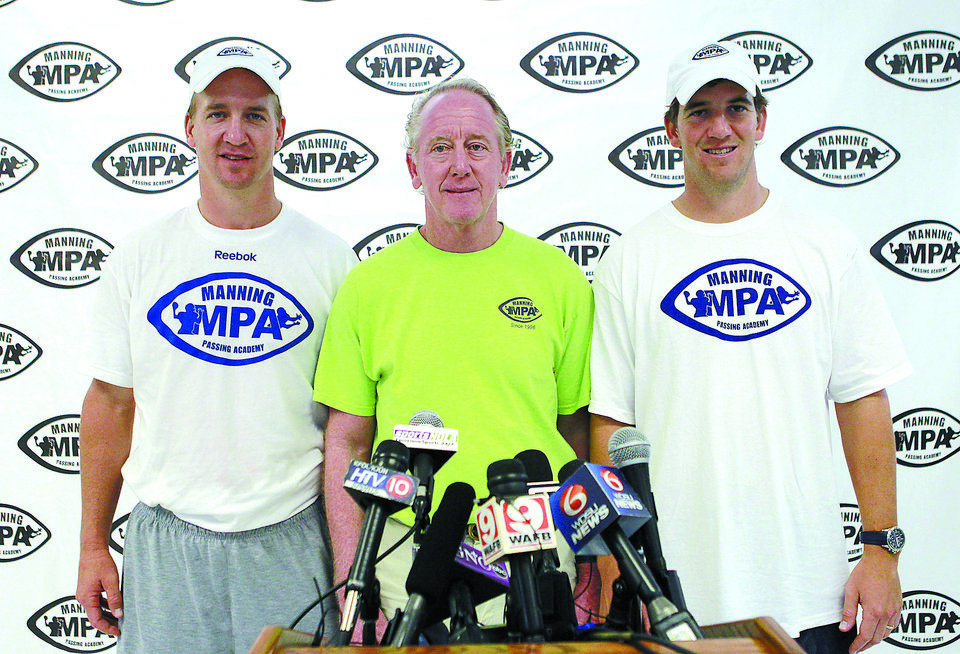 Denver Broncos quarterback Peyton Manning, left, and New York Giants quarterback Eli Manning, right,  pose for a photo-op with thier father, former NFL football quarterback Archie Manning, at the Manning Passing Academy at Nicholls State University in Thibodaux, La., Friday, July 13, 2012. (AP Photo/Gerald Herbert)