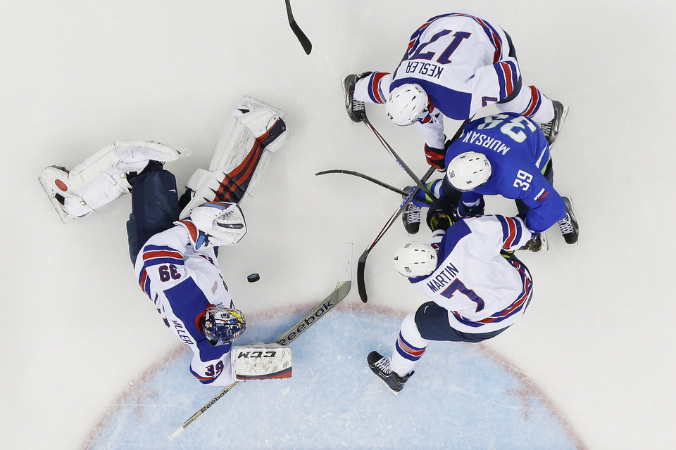 Photo - USA goaltender Ryan Miller reaches for the puck and USA forward Ryan Kesler (17) and defenseman Paul Martin (7) keep Slovenia forward Jan Mursak (39) away during the 2014 Winter Olympics men's ice hockey game at Shayba Arena Sunday, Feb. 16, 2014, in Sochi, Russia. (AP Photo/Matt Slocum)