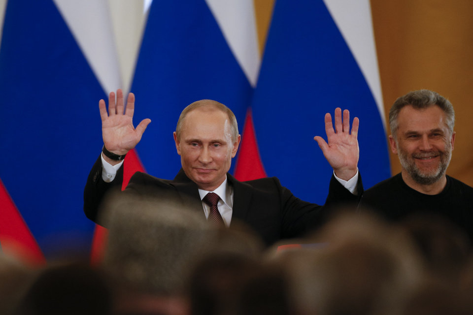 Photo - Russian President Vladimir Putin gestures after signing a treaty to incorporate Crimea into Russia in the Kremlin in Moscow,  Tuesday, March 18, 2014. President Vladimir Putin on Tuesday signed a treaty to incorporate Crimea into Russia, describing the move as the restoration of historic injustice and a necessary response to what he called the Western encroachment on Russia's vital interests. At right is Sevastopol mayor Alexei Chalyi.  (AP Photo/Alexander Zemlianichenko)