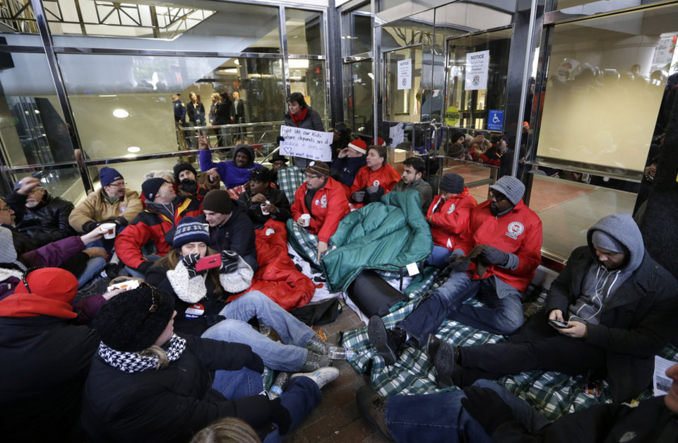 Protesters sit during a rally Tuesday outside the doors of the George W. Romney State Building, where Gov. Rick Snyder has an office, in Lansing, Mich. AP PHOTO <strong>Paul Sancya - AP</strong>
