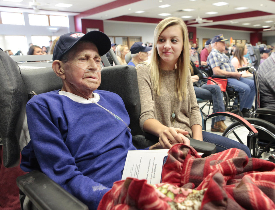 "Bayley Allen, right, from Noble High School, holds the hand of World War II veteran James Brown during the ""Operation 4G; Giving to the Grounded Greatest Generation"" ceremony Friday at the Oklahoma Department of Veterans Affairs Veterans Center in Norman.  <strong>David McDaniel - The Oklahoman</strong>"