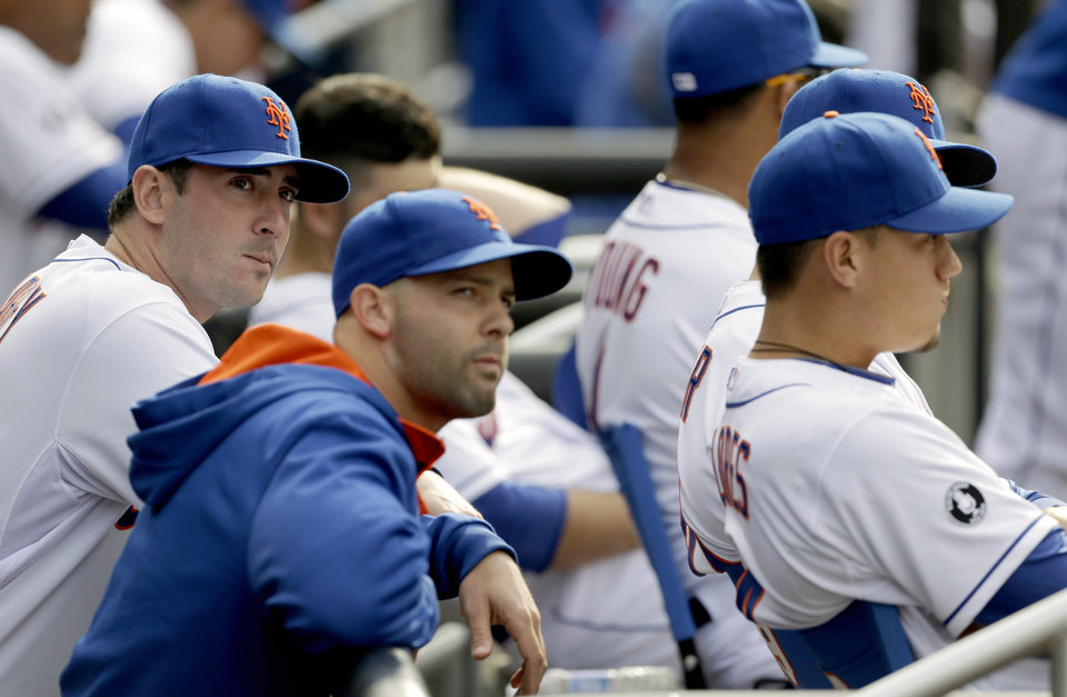 Members of the New York Mets pitching staff, including Matt Harvey, left, Dillon Gee, center, and Carlos Torres, sit in the dugout during the ninth inning of a baseball game against the Washington Nationals at Citi Field, Thursday, April 3, 2014, in New York. The Nationals defeated the Mets 8-2. (AP Photo/Seth Wenig)