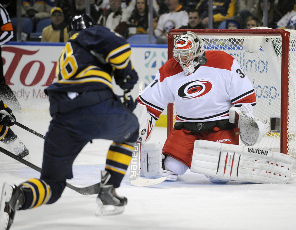 Photo - Buffalo Sabres' Zemgus Girgensons (28), of Latvia, shoots the puck off the mask of  Carolina Hurricanes' Anton Khudobin (31), of Russia, during the first period of an NHL hockey game in Buffalo, N.Y., Thursday, Jan. 23, 2014. (AP Photo/Gary Wiepert)