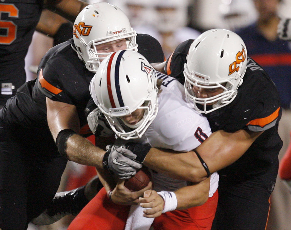 Photo - Oklahoma State's Caleb Lavey (45) and Cooper Bassett (80) bring down Arizona's Nick Foles (8) during a college football game between the Oklahoma State University Cowboys (OSU) and the University of Arizona Wildcats at Boone Pickens Stadium in Stillwater, Okla., Thursday, Sept. 8, 2011. Photo by Sarah Phipps, The Oklahoman  ORG XMIT: KOD
