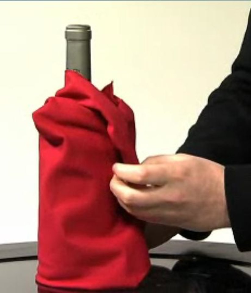 Photo - HOLIDAY HOW-TO / WRAPPING / STEP-BY-STEP / HOW TO WRAP A WINE BOTTLE IN A NAPKIN / WINE SWADDLE / DIRECTIONS ORG XMIT: 0812151600373112