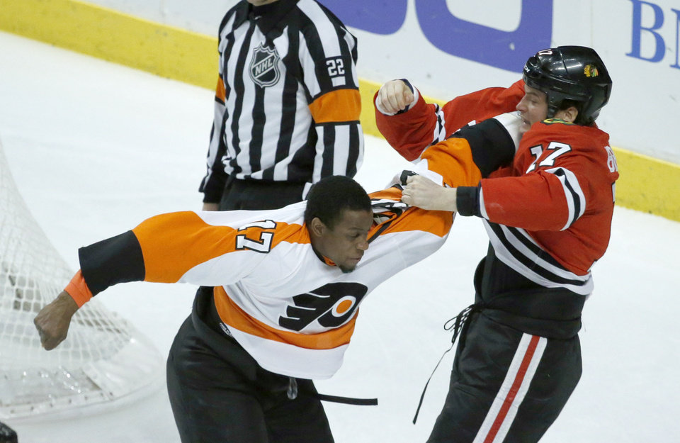 Photo - Philadelphia Flyers right wing Wayne Simmonds, left, and Chicago Blackhawks defenseman Sheldon Brookbank, right, fight during the first period of an NHL hockey game on Wednesday, Dec. 11, 2013, in Chicago. (AP Photo/Charles Rex Arbogast)