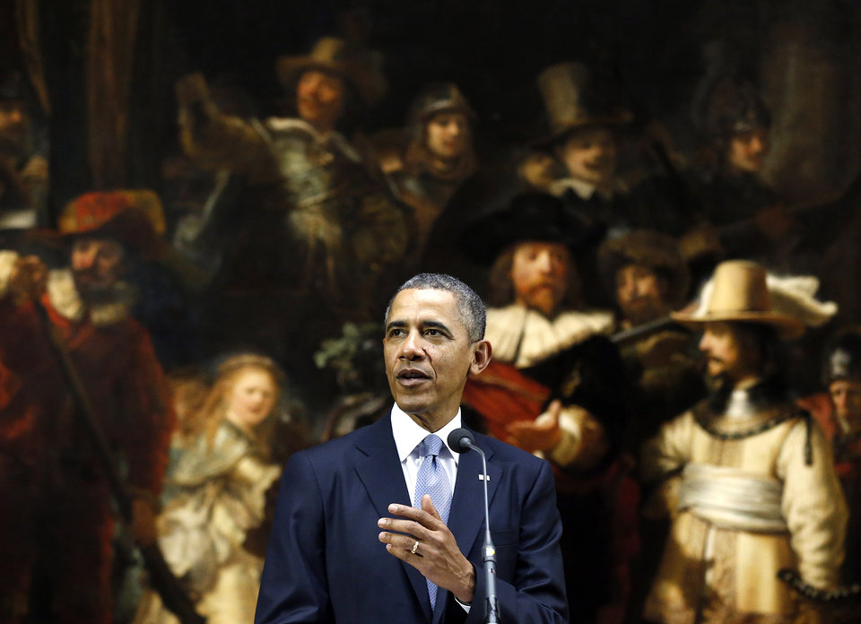 Photo - U.S. President Barack Obama delivers a statement in front of Dutch master Rembrandt's The Night Watch painting during a visit to the Rijksmuseum in Amsterdam, Netherlands, Monday, March 24, 2014. Obama will attend the two-day Nuclear Security Summit in The Hague. (AP Photo/Frank Augstein)