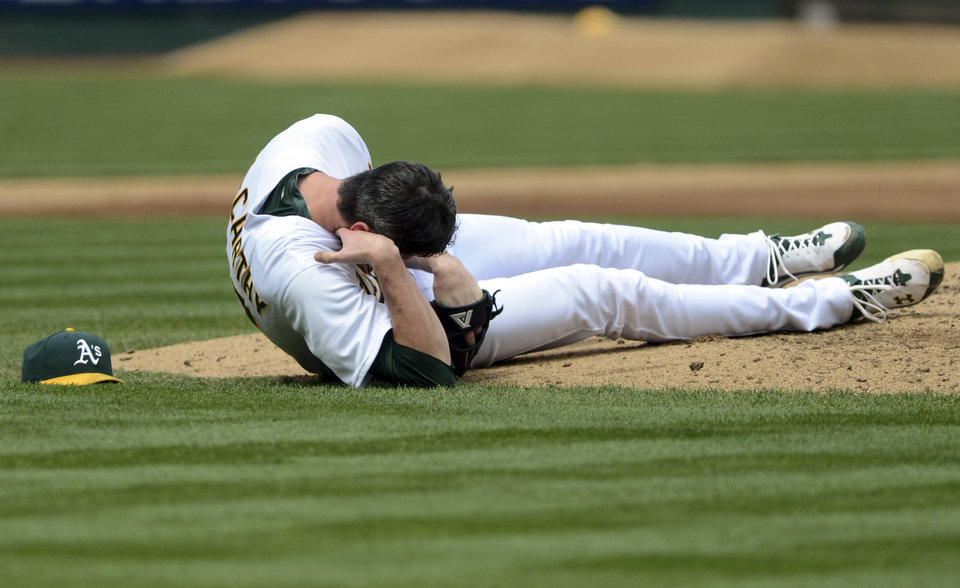 Photo -   Oakland Athletics pitcher Brandon McCarthy (32) holds his head after being struck by a ball hit by Los Angeles Angels' Erick Aybar in the fourth inning of a baseball game, Wednesday, Sept. 5, 2012, in Oakland, Calif. McCarthy was sent to the hospital, and according to the team he never lost consciousness. The Angels won 7-1. (AP Photo/The Contra Costa Times, Doug Duran)