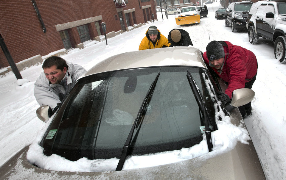 Photo - A group of men help push a sports car up a snow-covered street in the Old Port section of Portland, Maine, during a snow storm, Friday, Feb. 8, 2013. The storm is expected to dump up to two feet of snow on the region. (AP Photo/Robert F. Bukaty)