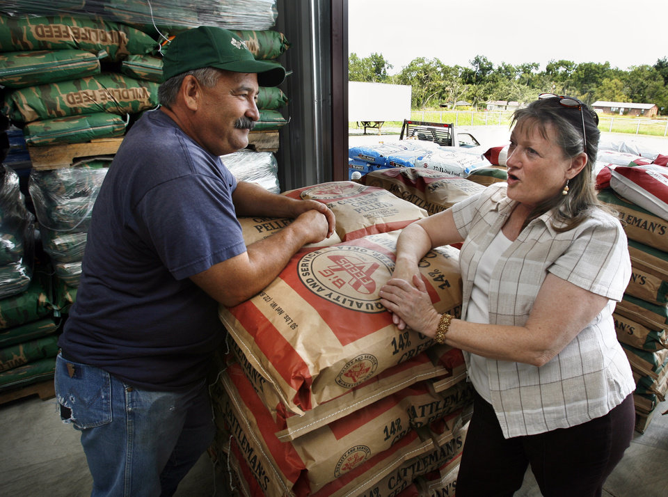 Photo - Melba Lee (right) owns the Lone Grove Feed and Supply store in Lone Grove, Okla. She talks with customer Dick Elliott on Tuesday, Sept. 1, 2009.   The store was damaged earlier in the year by a deadly tornado.  Photo by Steve Sisney, The Oklahoman ORG XMIT: KOD