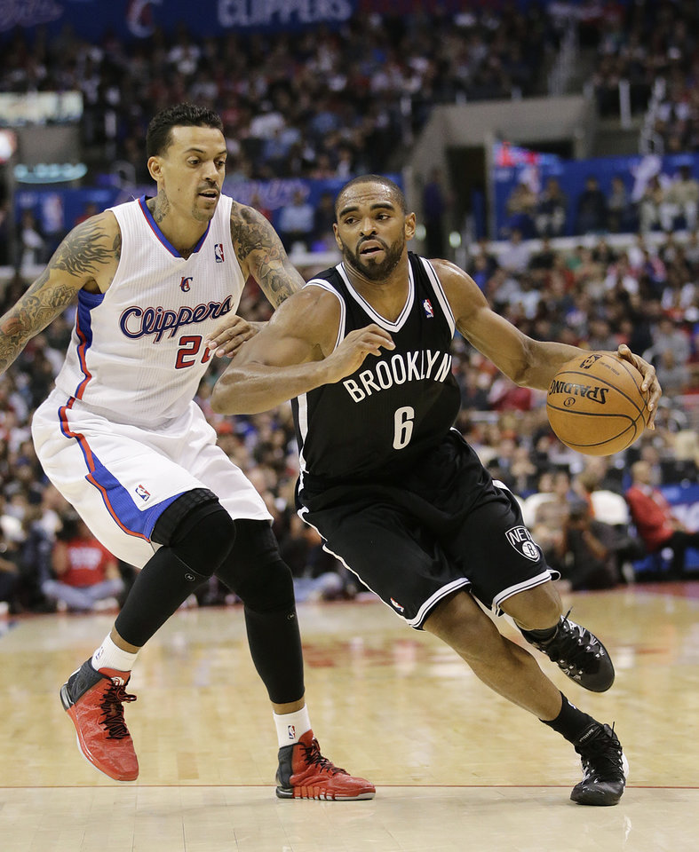 Photo - Brooklyn Nets' Alan Anderson, right, drives past Los Angeles Clippers' Matt Barnes during the second half of an NBA basketball game on Saturday, Nov. 16, 2013, in Los Angeles. (AP Photo/Jae C. Hong)