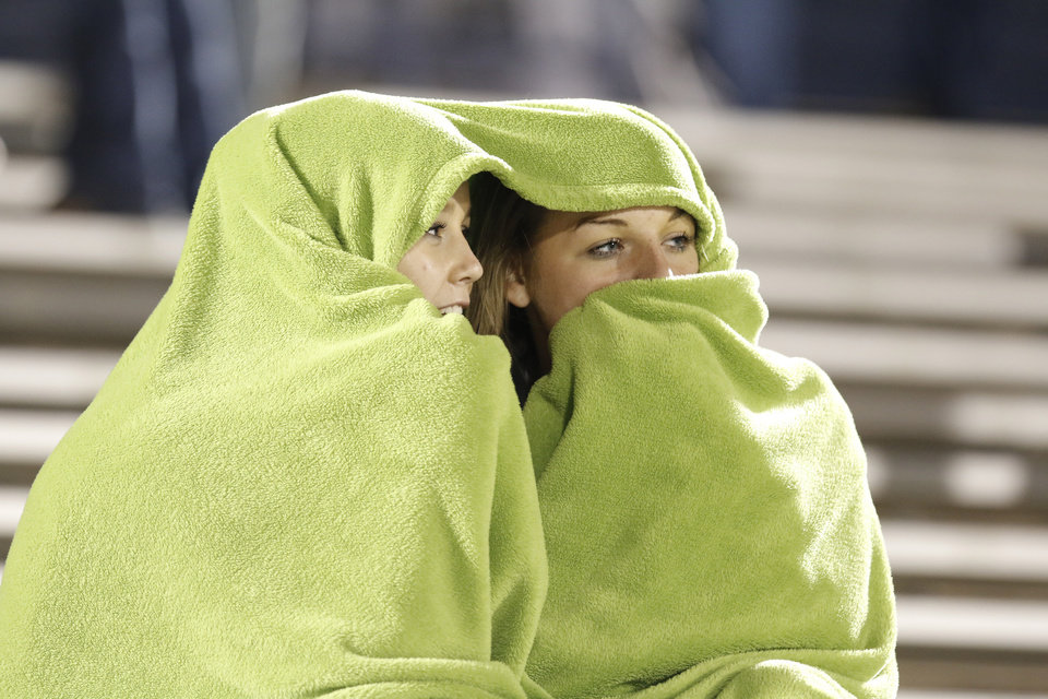Edmond Memorial fans Andee Decker and Makayla White try to stay warm during halftime during the high school football playoff game between Edmond North and Edmond Memorial at Watland Stadium in Edmond, Friday, November 15, 2013. Photo by Doug Hoke, The Oklahoman