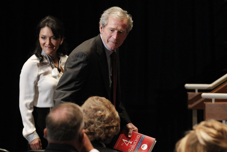 Photo - Former President George W. Bush arrives to give opening remarks at the Federal Reserve Bank of Dallas for a conference titled