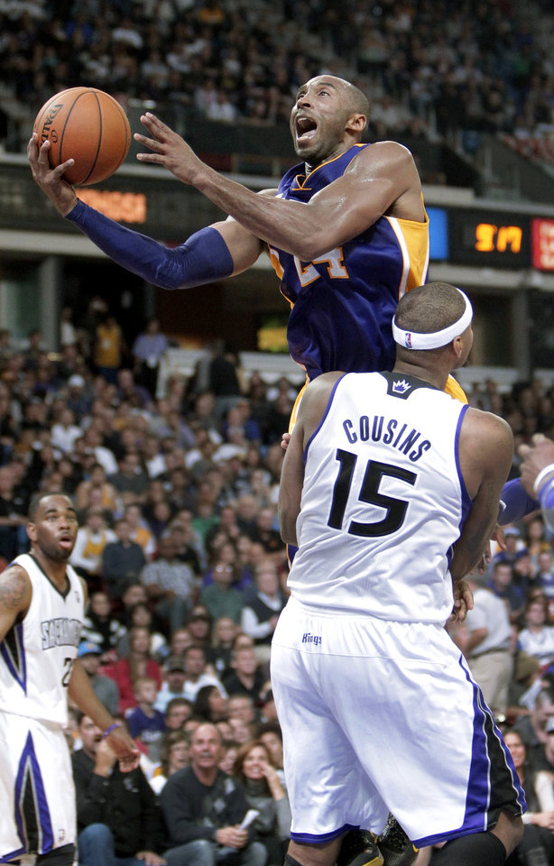 Photo -   Los Angeles Lakers guard Kobe Bryant is fouled by Sacramento Kings center DeMarcus Cousins as he drives to the basket during the second half of an NBA basketball game in Sacramento, Calif., Wednesday, Nov. 21, 2012. The Kings won 113-97. (AP Photo/Rich Pedroncelli)