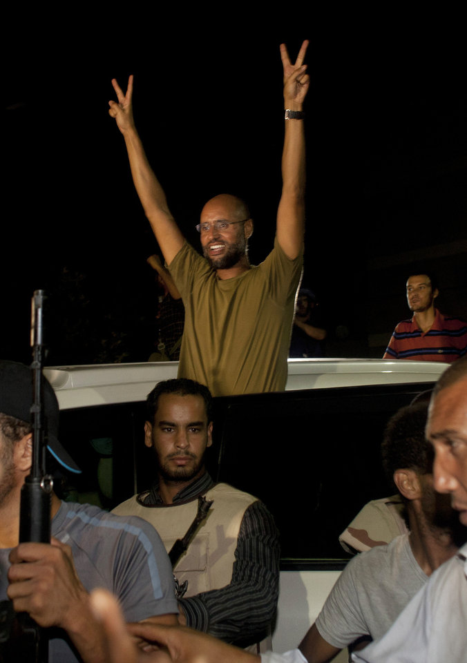 Moammar Gadhafi's son, Seif al-Islam waves to troops loyal to his father in Tripoli, Libya, Tuesday, Aug. 23, 2011. Al-Islam, who was earlier reported arrested by Libya's rebels, turned up early Tuesday morning at the hotel where foreign journalists stay in Tripoli, then took reporters in his convoy on a drive through the city. (AP Photo/Dario Lopez-Mills)