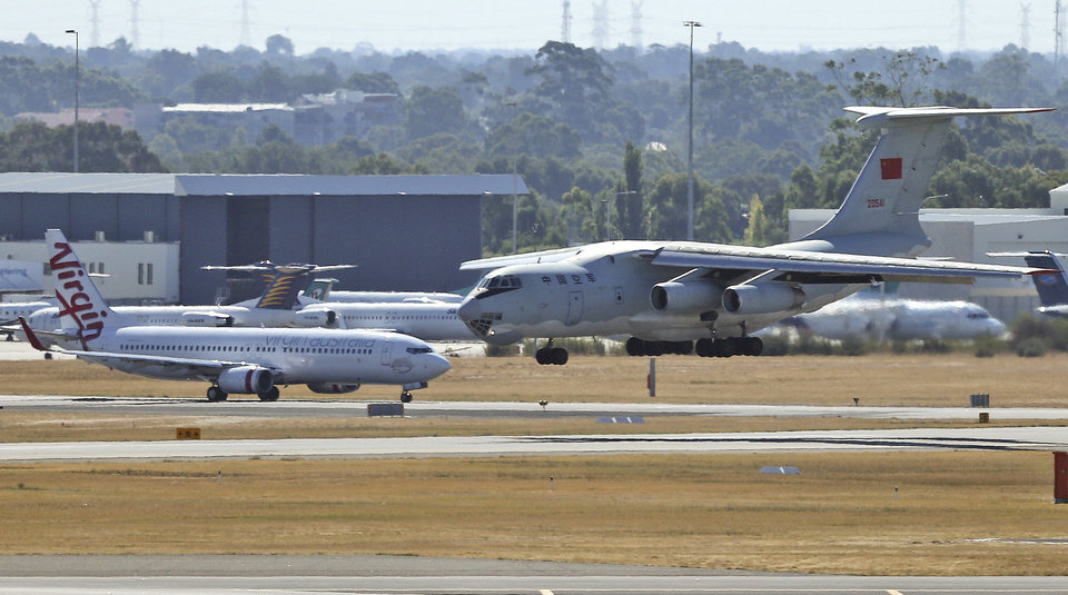 Photo - A Chinese  Ilyushin IL-76 aircraft, right, lands at Perth International Airport after returning from the ongoing search operations for missing Malaysia Airlines Flight 370 in Perth, Australia, Sunday, April 13, 2014. Following four strong underwater signals in the past week, all has gone quiet in the hunt for the missing Malaysian airline, meaning the batteries on the all-important black boxes may have finally died. Despite having no new pings to go on, crews are continuing their search Sunday for debris and any sounds that could still be emanating. (AP Photo/Rob Griffith)