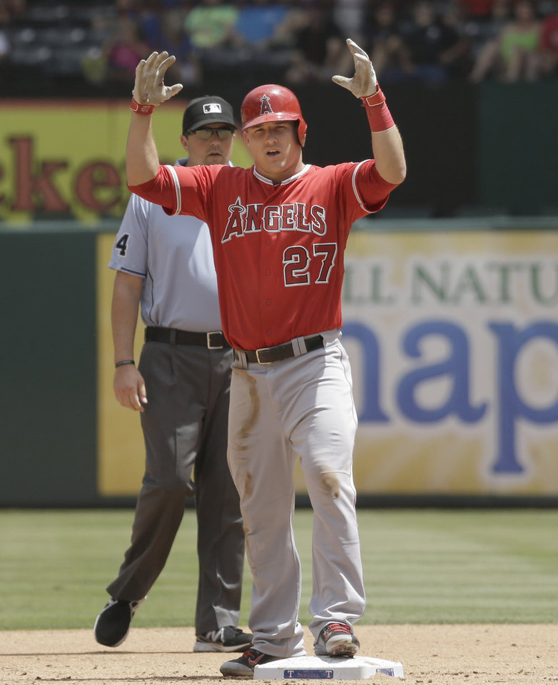 Photo - Los Angeles Angels Mike Trout reacts and gestures to towards his dugout from second base after hitting an RBI double  during the fourth inning of a baseball game against the Texas Rangers in Arlington, Texas, Sunday, July 13, 2014.  The Angels won 10-7. (AP Photo/LM Otero)