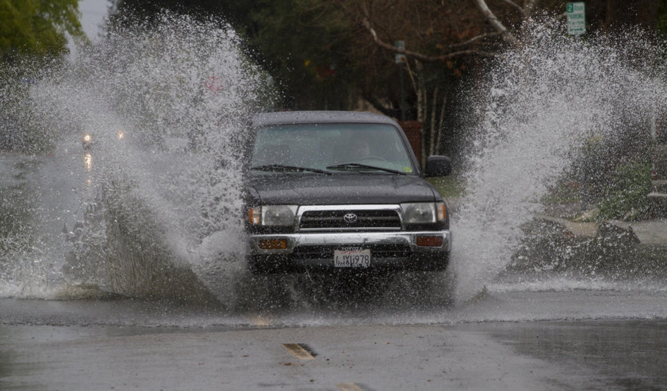Photo - A SUV drives through a flooded portion of a street in Encino, section of Los Angeles Friday, Feb. 28, 2014.  The first wave of a powerful Pacific storm spread rain and snow early Friday through much of California, where communities endangered by a wildfire just weeks ago now faced the threat of mud and debris flows.  (AP Photo/Ringo H.W. Chiu)