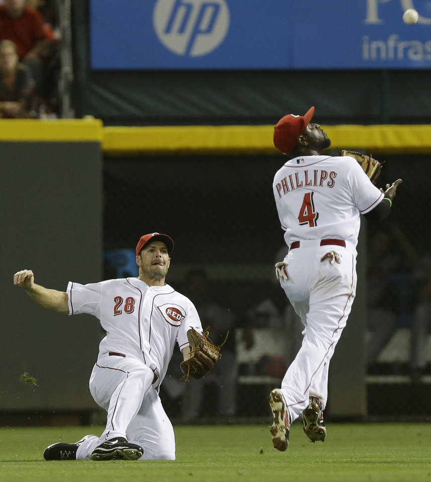 Photo - Cincinnati Reds second baseman Brandon Phillips (4) catches a pop fly hit by Atlanta Braves' Justin Upton as right fielder Chris Heisey (28) slides to avoid a collision in the fourth inning of a baseball game, Saturday, Aug. 23, 2014, in Cincinnati. (AP Photo/Al Behrman)