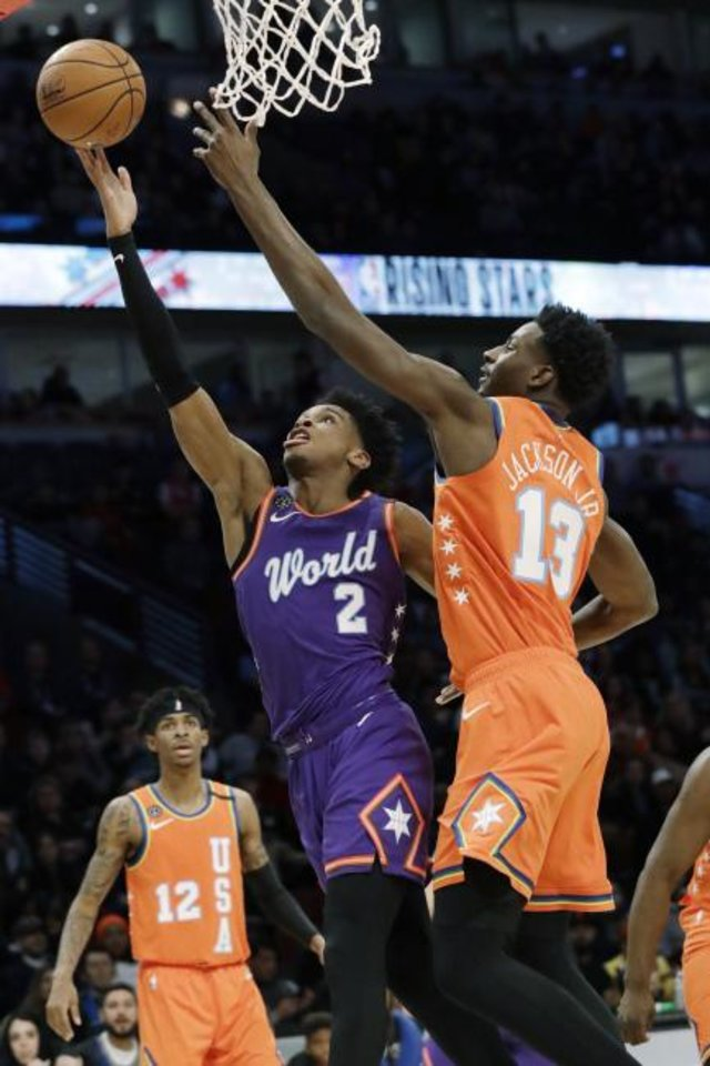 Photo -  World's Shai Gilgeous-Alexander, left, of the Oklahoma City Thunder, shoots against the U.S. forward Jaren Jackson Jr., of the Memphis Grizzlies, on Friday during the NBA Rising Stars basketball game in Chicago. [Nam Y. Huh/The Associated Press]