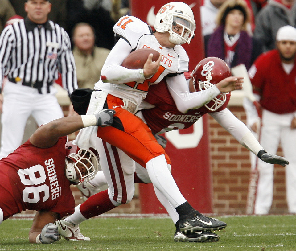 Photo - Oklahoma State's Zac Taylor (11) is hit by Oklahoma's Adrian Taylor (86) and Ryan Reynolds (8) during the first half of the college football game between the University of Oklahoma Sooners (OU) and the Oklahoma State University Cowboys (OSU) at the Gaylord Family-Memorial Stadium on Saturday, Nov. 24, 2007, in Norman, Okla.  Photo By Bryan Terry, The Oklahoman