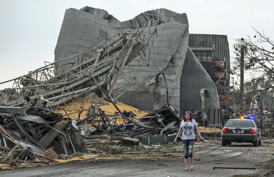Photo - A woman walks down Black Hills Trail road in Pilger, Neb., Monday, June 16, 2014. At least one person is dead and at least 16 more are in critical condition after two massive tornadoes swept through northeast Nebraska on Monday. (AP Photo/Mark 'Storm' Farnik)