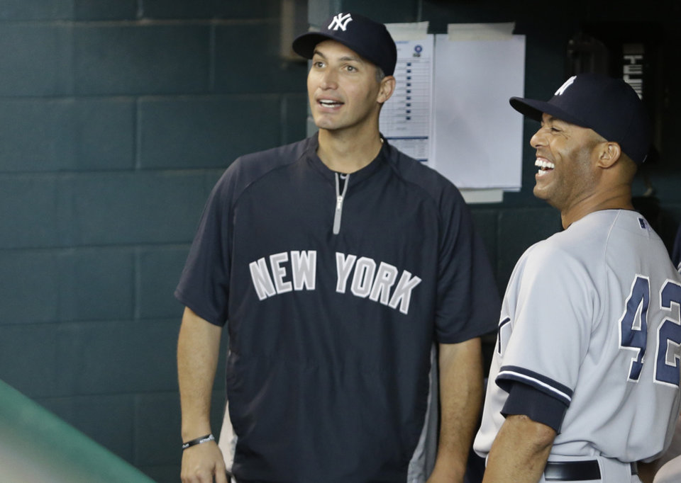 Photo - New York Yankees Andy Pettitte, left, and Mariano Rivera smile as they watch a video tribute to Rivera from the dugout before the baseball game against the Houston Astros Sunday, Sept. 29, 2013, in Houston. Both players are retiring from the major leagues. (AP Photo/Richard Carson)