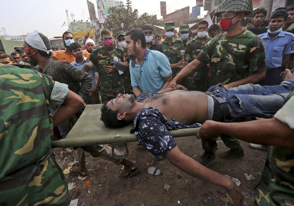 Photo - A Bangladeshi garment worker who was pulled alive from the rubble is rushed on a stretcher at the site of a building that collapsed Wednesday in Savar, near Dhaka, Bangladesh, Friday, April 26, 2013. The death toll reached hundreds of people as rescuers continued to search for injured and missing, after a huge section of an eight-story building that housed several garment factories splintered into a pile of concrete.(AP Photo/Kevin Frayer)