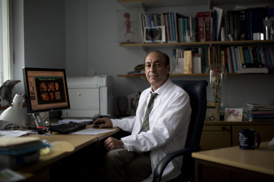 Photo - Professor Alexander Seifalian poses for a portrait in his office at his research facility in the Royal Free Hospital in London, Monday, March 31, 2014. In the north London hospital, scientists are growing noses, ears and blood vessels in the laboratory in a bold attempt to make body parts using stem cells. It is among several labs around the world, including in the U.S., that are working on the futuristic idea of growing custom-made organs in the lab. While only a handful of patients have received the British lab-made organs so far— including tear ducts, blood vessels and windpipes — researchers hope they will soon be able to transplant more types of body parts into patients, including what would be the world's first nose made partly from stem cells.