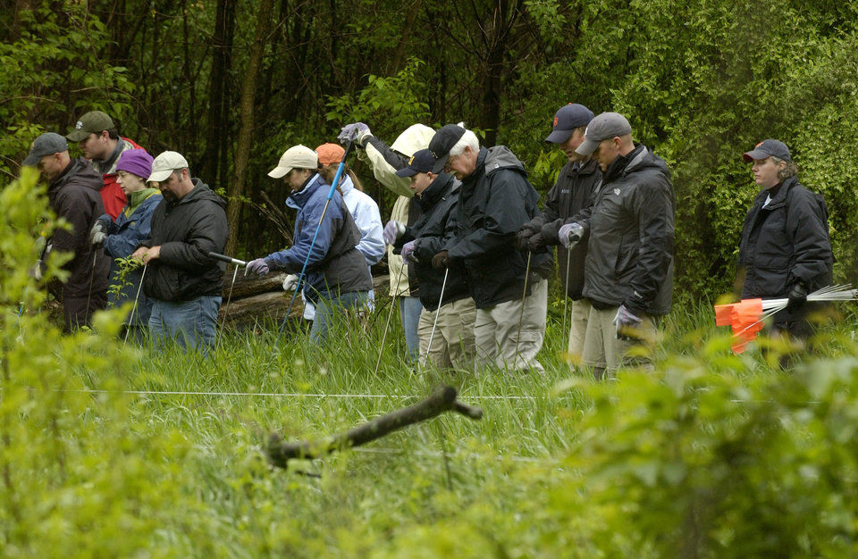 Photo -   FILE - In this May 19, 2006, file photo, searchers in formation inspect a field at Hidden Dreams Farm in Milford Township, Mich., where federal agents are digging for the body of former Teamsters leader Jimmy Hoffa. Hoffa's mysterious disappearance, assumed death and myriad searches for his body have been the stuff of urban legends for more than three decades. (AP Photo/John M. Galloway, File)