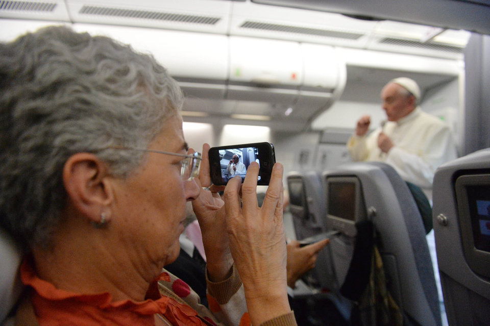"A journalist takes a photo of Pope Francis speaking during a news conference aboard the papal flight on the journey back from Brazil, Monday, July 29, 2013. Pope Francis reached out to gays on Monday, saying he wouldn't judge priests for their sexual orientation in a remarkably open and wide-ranging news conference as he returned from his first foreign trip. ""If someone is gay and he searches for the Lord and has good will, who am I to judge?"" Francis asked. His predecessor, Pope Benedict XVI, signed a document in 2005 that said men with deep-rooted homosexual tendencies should not be priests. Francis was much more conciliatory, saying gay clergymen should be forgiven and their sins forgotten. Francis' remarks came Monday during a plane journey back to the Vatican from his first foreign trip in Brazil. (AP Photo/Luca Zennaro, Pool)"
