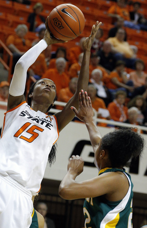 Photo - Oklahoma State's Toni Young (15) shoots over Vermont's Tierra Shumpert (22) during the women's college basketball game between Oklahoma State University and Vermont at Gallagher-Iba Arena in Stillwater, Okla., Sunday,Dec. 16, 2012. Photo by Sarah Phipps, The Oklahoman