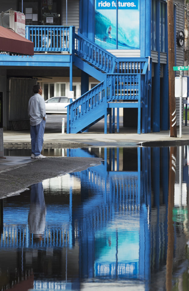 Photo - Residents looks at the overflowed Pacific Coast Highway in the Sunset Beach area of Huntington Beach, Calif., Thursday, Dec. 13, 2012. Astronomical high tides have caused minor street flooding in some low-lying areas along the Southern California coast. (AP Photo/Damian Dovarganes)